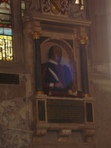 The bust is on the left (north) wall behind the altar rail. It is so constantly being photographed, that it is hard to avoid the glare of other cameras. The blue central light in this image is caused by someone else's camera.