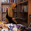 A woman looking through books in Afghanistan