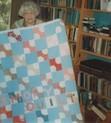 Margaret Sutton holding her patchwork quilt at Wild Wolf farm.
