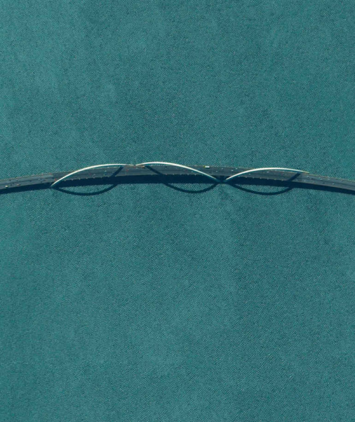 a strip dark gray bridge over a teal ocean. it has thin silver arches.