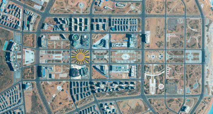 a city grid, mostly sandy or grey concrete. in the center there's a city block with a yellow circle which has yellow, tan, and grey lines going outwards, which looks like a child's drawing of a sun.