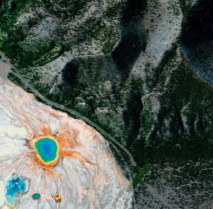 green mountains with trees and circular hot spring atop orange and grey rock. the spring is made up of concentric circles which look rainbow.